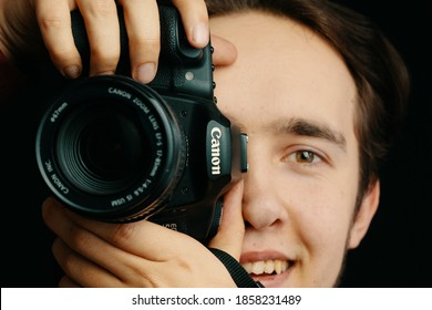 Smiling man takes pictures on Canon camera and tries to focus the lens and takes pictures. Photo editor, cameraman, journalist. Bishkek, Kyrgyzstan - December 15, 2019.