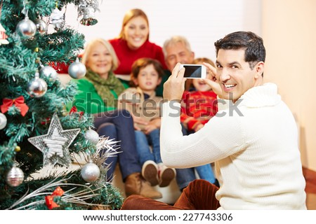 Smiling man taking family picture at christmas with his smartphone camera