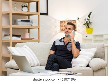 Smiling man taking mobile or smart phone and starting talking over it. Picture of handsome young man sitting on sofa at home and looking in front of him.