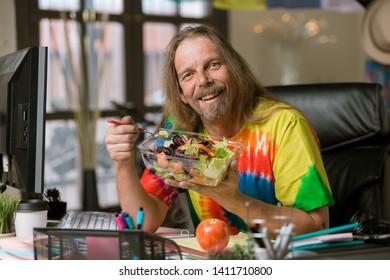 Smiling man in tie dye shirt eating healthy food at his desk
