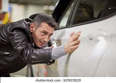 Smiling man touches surface of white modern car with his palm at underground parking.