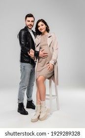 Smiling man touching belly of stylish pregnant wife on chair on grey background