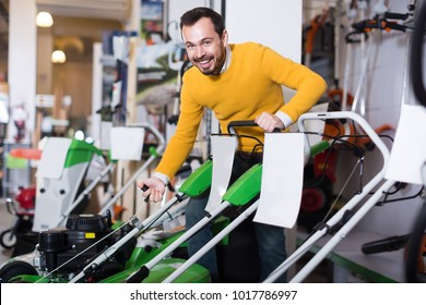 Smiling man tries to start a lawnmower in a garden tools store