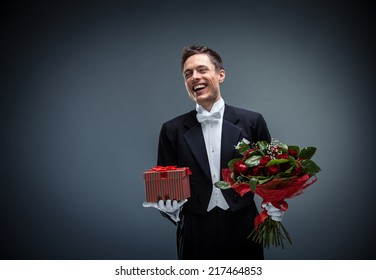 Smiling man in a tuxedo with a bouquet and gifts