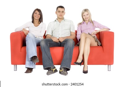 Smiling man and two women sitting on a red couch.  Isolated on white background, in studio.