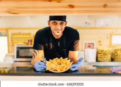 Smiling man in uniform smiling at camera and showing order standing in food truck.