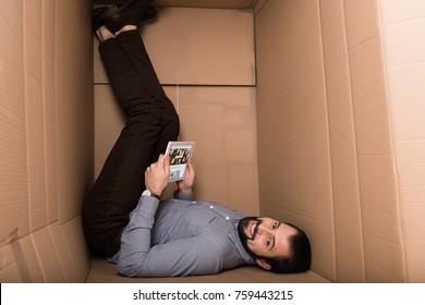 smiling man using digital tablet with depositphotos website in cardboard box