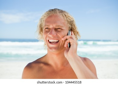 Smiling man using his mobile phone while standing in front of the ocean