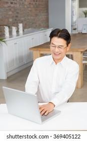 Smiling man using laptop in living room