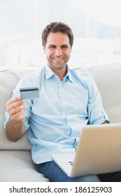Smiling man using laptop sitting on sofa shopping online at home in the living room