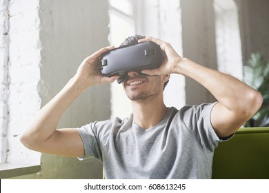 Smiling man using oculus rift headset, experiencing virtual reality while playing video game sitting on green sofa at home. European male holding with hands 3d glasses in modern coworking studio