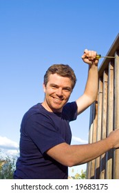 Smiling man using screwdriver to fix porch. Vertically framed photo.
