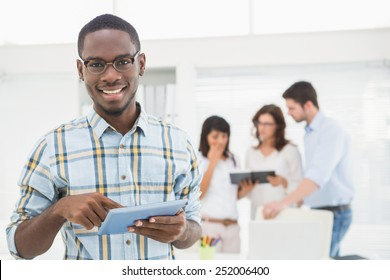 Smiling man using tablet in front of his colleagues in the office