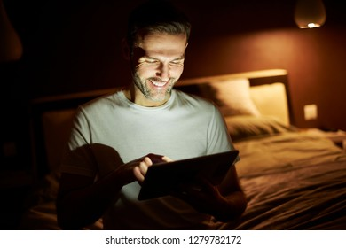 Smiling man using a  tablet at night