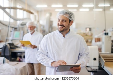 Smiling man using tablet while standing in food factory.
