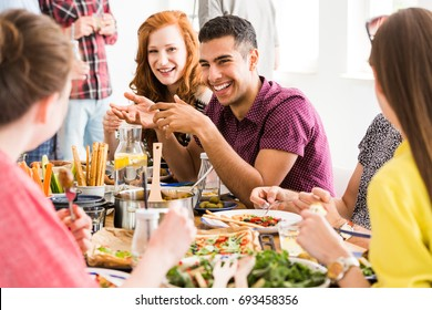 Smiling man in violet shirt eats slow food with happy vegetarians in vege restaurant