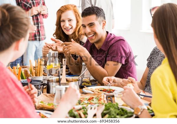 Smiling man in violet shirt eats slow food with happy vegetarians in vege restaurant