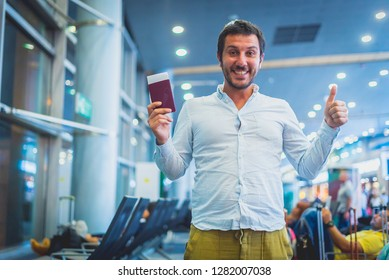 smiling man waiting in the airport, holding tickets and passport and saying OK