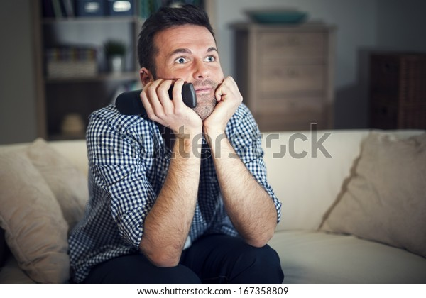 Smiling man watching interesting movie