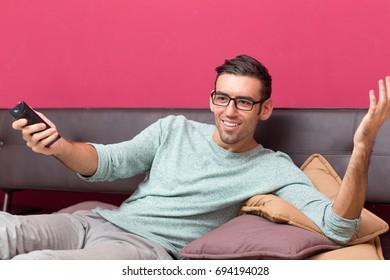 Smiling Man Watching Interesting Program on TV