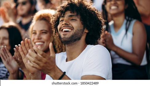 Smiling man watching a soccer match and applauding at stadium. Excited sports fans applauding and celebrating their team's victory.
