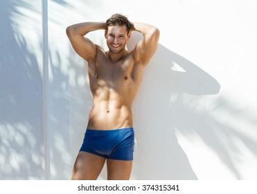 Smiling man wear blue swimming trunks