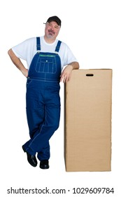 Smiling man wearing dungarees leaning against large cardboard box on white background