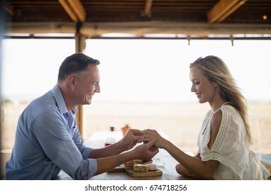 Smiling man wearing engagement ring to woman in restaurant