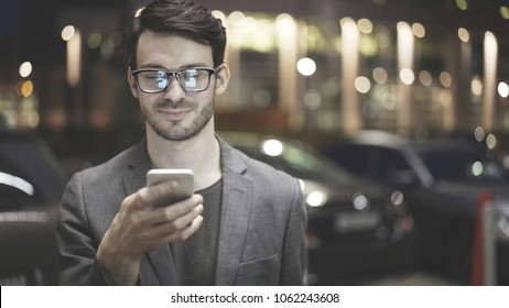 A smiling man wearing eyeglasses is holding scrolling texting in his cellphone. A smiling man calls for a taxi in an app.