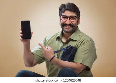 Smiling man wearing eyeglasses pointing towards a mobile phone which is held in other hand.