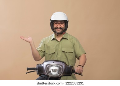 Smiling man wearing helmet sitting on a scooter and showing palm.