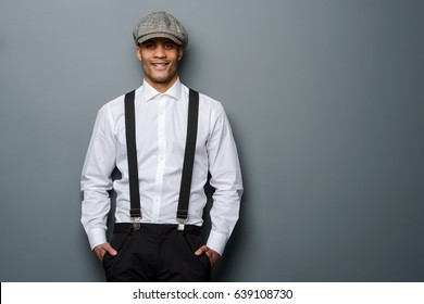 Smiling man wearing white shirt, suspenders and flat cap, close-up. Grey background, place to insert your text. Positive hipster.