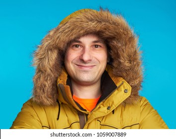 smiling man wearing yellow winter coat. Looking at camera. Isolated on blue background