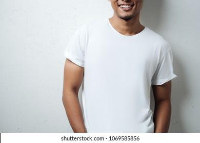 smiling man in white blank t-shirt, grunge wall, studio close-up