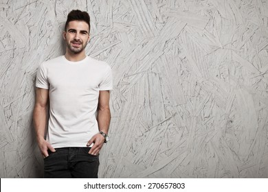 Smiling man in white blank t-shirt, and OSB wooden wall background