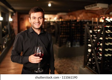 Smiling man in the wine cellar