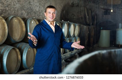 Smiling man wine technician working in storage with wooden barrels