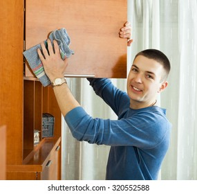 Smiling man wiping dust from wooden chest at home
