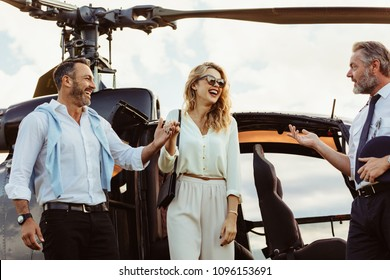 Smiling man and woman alighted from a private helicopter with pilot standing by. Couple getting off a private aircraft with mature pilot.