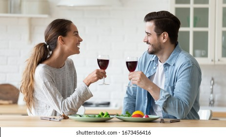 Smiling man and woman chatting, drinking red wine in modern kitchen, happy wife and husband holding glasses, sitting at table, celebrating anniversary, romantic date or spending weekend at home