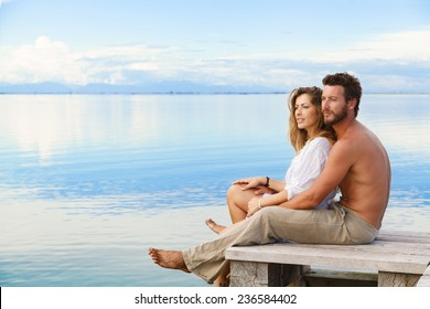 Smiling man and woman couple sitting on a Jetty under a blue cloudy sky