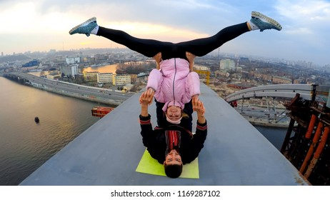 Smiling man and woman doing acrobatic yoga stunts on bridge, adrenaline junkies