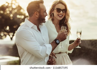 Smiling man and woman enjoying a glass of wine outdoors. Happy couple with a glass of wine sitting outdoors.