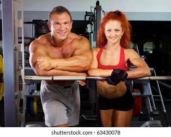 Smiling man and woman at the gym apparatus in a health club