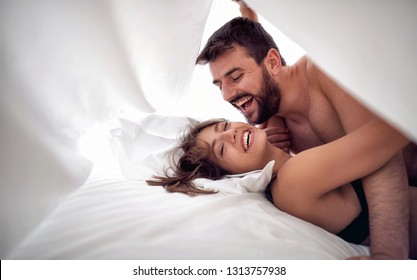 Smiling man and woman lovers having sex on a bed in morning
