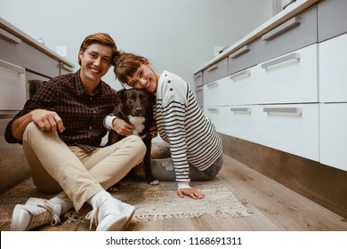 Smiling man and woman sitting on floor at home with their pet dog. Portrait of happy dog loving family with their pet dog.