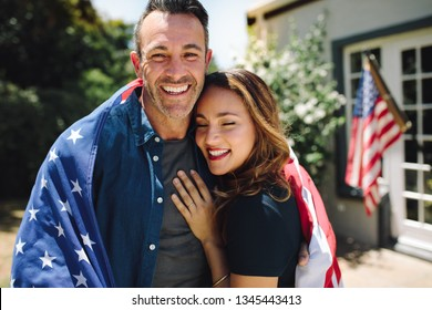 Smiling man and woman standing in their backyard with the american flag in the background. Happy couple standing together with the american flag on their shoulders.