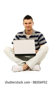 A smiling man working with a laptop on the floor, over white