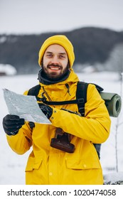 Smiling man in yellow jacket stands with a map in his arms somwhere in the mountains