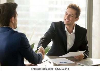 Smiling manager and client handshaking, satisfied businessmen shaking hands offering financial contract, support, help, good business deal, reaching agreement, business analytics, graphs stats on desk